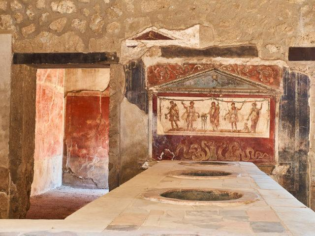 Dolias (sunk into the counter) and fresco detail of archaeological remains of thermopolium of Vetutius Placidus, at Ruins of Pompeii, Italy