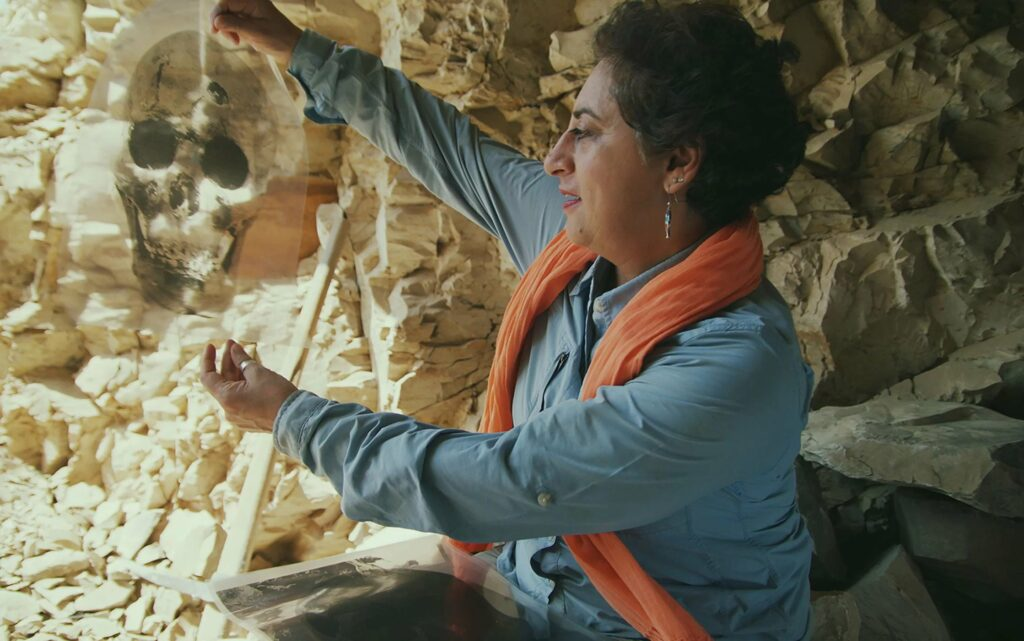 Archaeologist Salima Ikram examines an image of a skull from the mass burial.