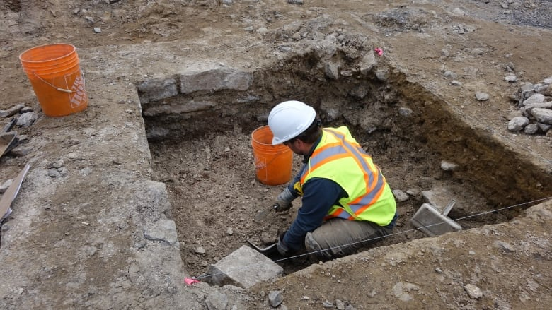 A worker sifts through the remnants of the site of the old guardhouse and jail cells just east of Centre Block. A variety of items have been found there, including pins and chin straps.