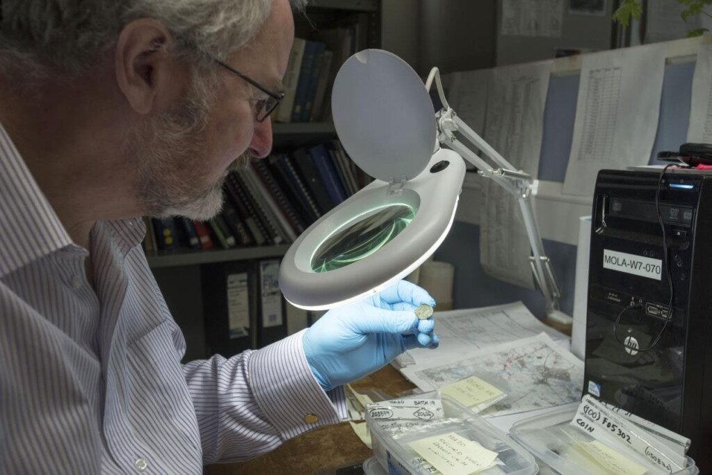 Dr Julian Bowsher examines the rare coin.